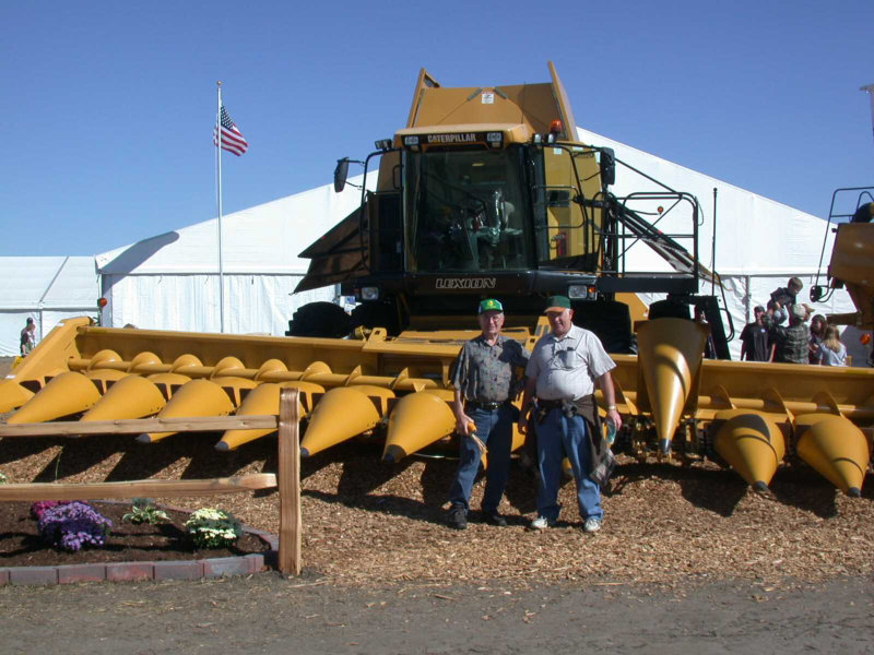 Emil and John in front of a corn harvester